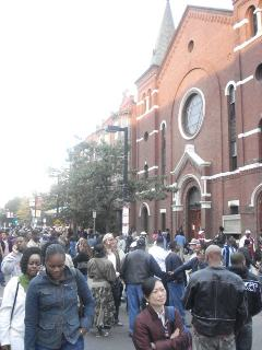 a mixed crowd walks past the church
